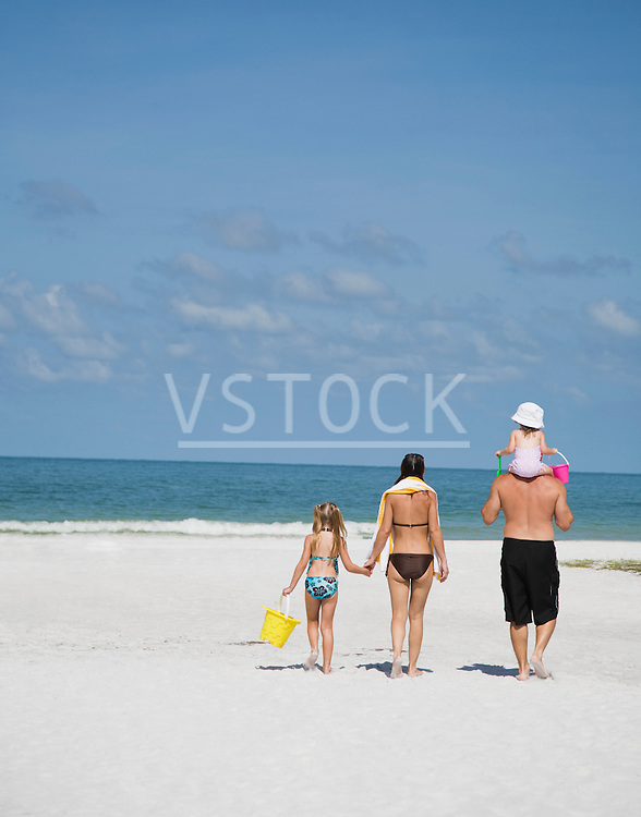 USA, Florida, Family with two daughters (3-4, 5-9) walking on beach, rear view