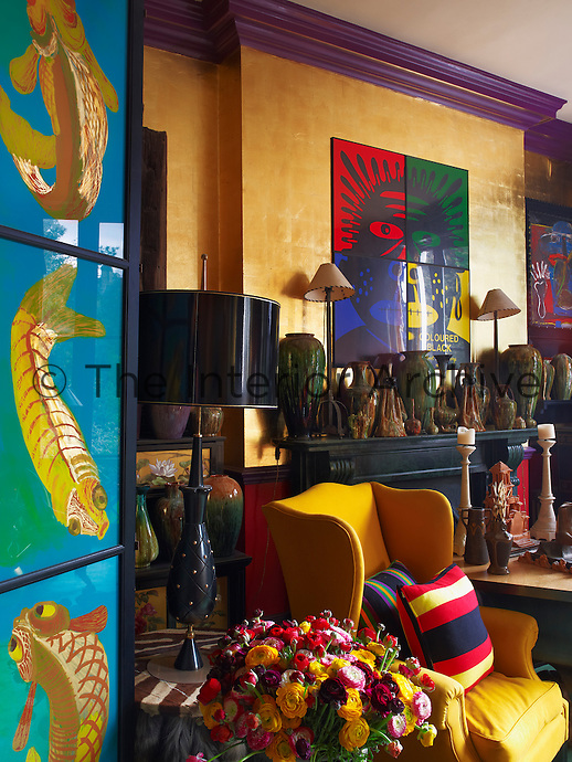 Every flat surface in the colourful sitting room is filled with pottery and the artwork above the fireplace is by Gilbert & George