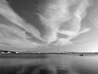 Soft clouds streak across the sky above Newport Bridge