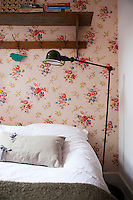 A cheerful floral wallpaper brings an accent of colour to the master bedroom