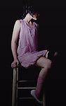 A young woman wearing a short purple dress sitting on a stool
