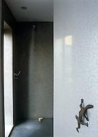 This wet room has concrete walls and a gecko door handle