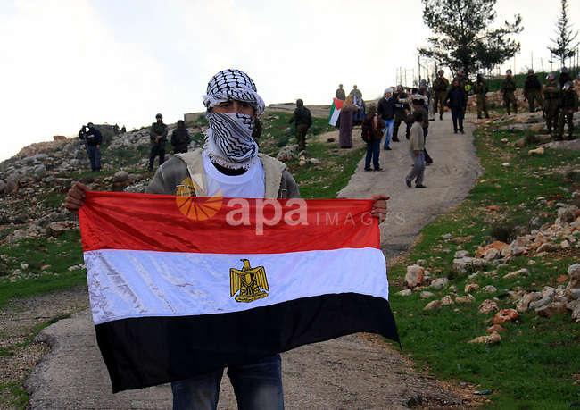 A Palestinian protester holds an Egyptian flag during the weekly demonstration against Israel's separation barrier in the West Bank village of Bilin near Ramallah, Friday, Feb. 11, 2011. Photo by Wagdi Eshtayah