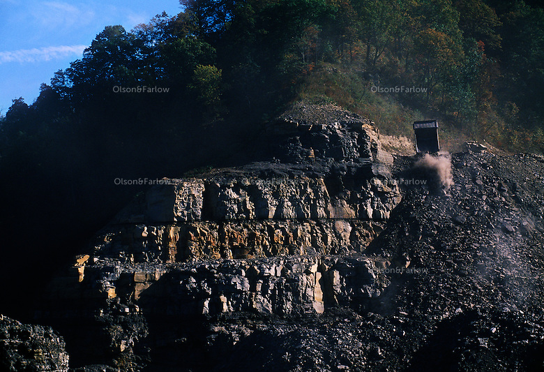 A truck backs onto a rock cliff and dumps a load of overburden or excess rock at a mountaintop removal mine site.
