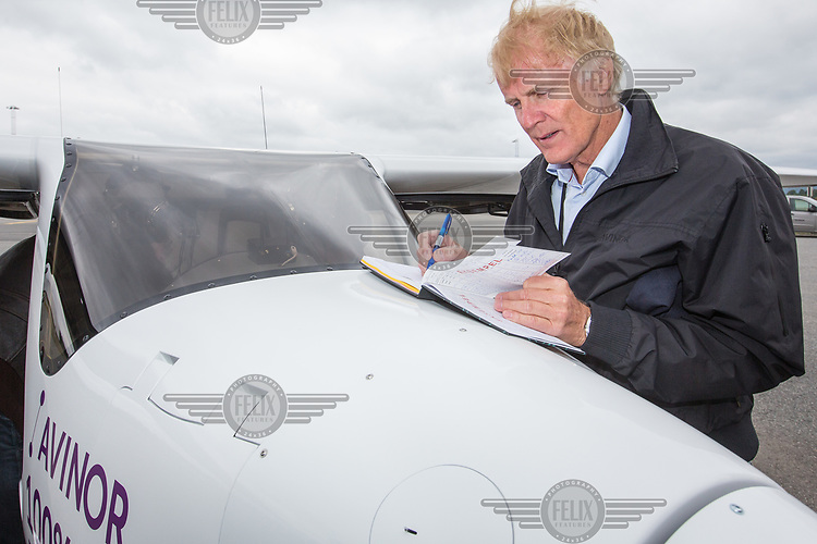 June 18th 2018 saw the first official flight by an electric aircraft in Norway. <br /> <br /> Civil Aviation Authority (Avinor) CEO Dag Falk-Petersen writes in the log book after taking  Minister of Transport and Communications Ketil Solvik-Olsen for a short flight around Gardermoen Airport. <br /> <br /> The plane is battery operated and signals a focus on more envorinmentally friendly solutions for the fututre. The project is supported by the government, and the project partners are Wider&oslash;e, SAS, the Norwegian Association of Air Sports, and climate foundation ZERO.<br /> <br />  &copy; Fredrik Naumann/Felix Features
