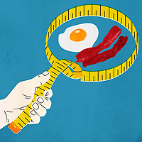 Hand holding tape measure around bacon and egg ExclusiveImage