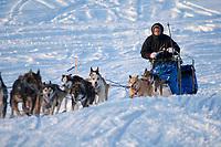 Sebastian Schnuelle runs up the bank of the Yukon River to Anvik during Iditarod 2009