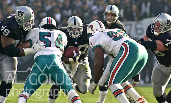 Oakland Raiders vs. Miami Dolphins at Oakland Alameda County Coliseum Saturday, January 6, 2001.  Raiders beat Dolphins  27-0.  Miami Dolphins linebacker Zack Thomas (54) and defensive tackle Daryl Gardener (92) attempt to block Oakland Raiders running back Tyrone Wheatley (47).