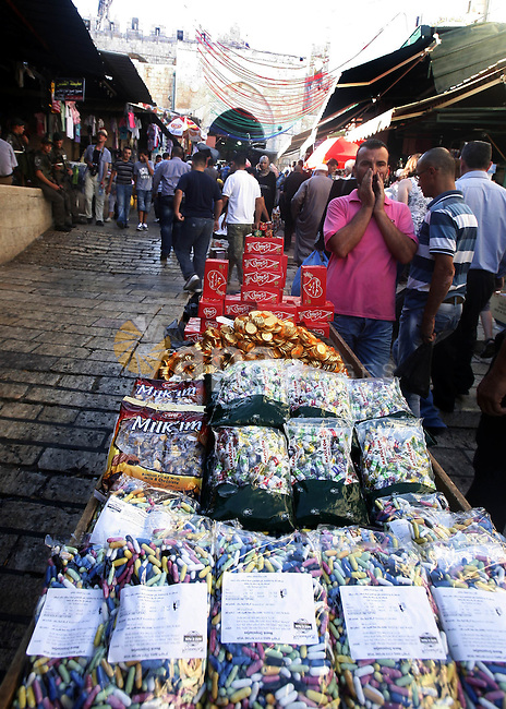A Palestinian vendor sells candy in the market during preparations for the Eid Al-Fitr feast in Jerusalem's Old City on Aug 16, 2012, as Muslims over the world prepare to celebrate Eid al-Fitr, a three day holiday marking the end of the religious month of Ramadan in which believers abstain from food and water during daylight hours. Photo by Mahfouz Abu Turk
