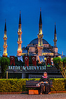 Fine Art Print Photography. World cultures. A night scene photograph of a Turkish woman sitting on a park bench in front of a Mosque in Istanbul, Turkey.<br />