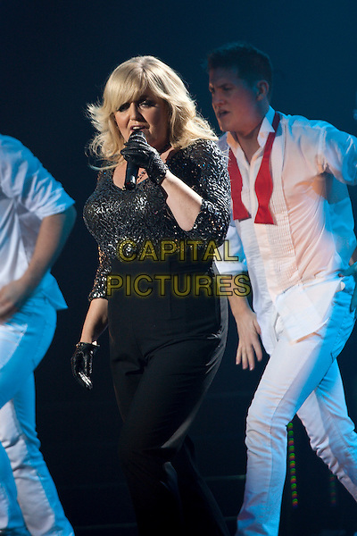 THE NOLANS - LINDA NOLAN.The Nolans in concert, Manchester Apollo Theatre, Manchester, England. .October 13th, 2009.half length stage concert live gig performance music black top singing gloves 3/4.CAP/AT.© Alan Towse/Capital Pictures.