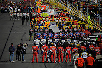 Crews in line along pit lane for the National Anthem.