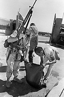 U.S. Marine Lance Cpl. Shawn Thacker checks the bag of a Somalia laborer before the man exits the U.S. embassy compoun in Mogadishu, Somalia, Feb., 1993. A number of Somalis worked for U.S. personel withing compounds doing general labor during Operation Restore Hope, a U.N. mission to stop starvation in the country.