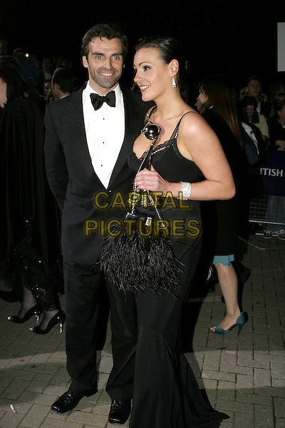 SURANNE JONES.National Television Awards, Royal Albert Hall..October 26th, 2004.award, trophy, full length, black feather bag, purse.www.capitalpictures.com.sales@capitalpictures.com.© Capital Pictures.