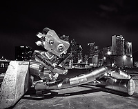 The traveling man in black and white takes a break to wait on the train playing his banjo with the Dallas skyline in the background at night. This is one part of the story of the traveling man robo sculpture in the city downtown in the as part known as Deep Ellum  The statues is meant to represent the railroad history of the area by the polished metal and rivets are all part of the history of the ares.