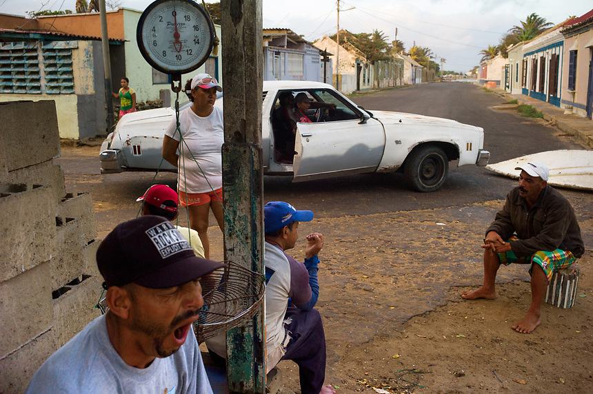 Fishermen and fishmongers await the morning catch in the colonial village of Adícora on Venezuela's Paraguaná Peninsula, Dec. 12, 2015. The remote desert peninsula in the Caribbean Sea lays bare the effects of Venezuela's politicized economy after 17 years under Hugo Chavez and successor Nicolas Maduro.