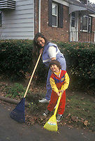 Mother and child son working in the garden, raking leaves together in autumn fall with toy wheelbarrow and child tools