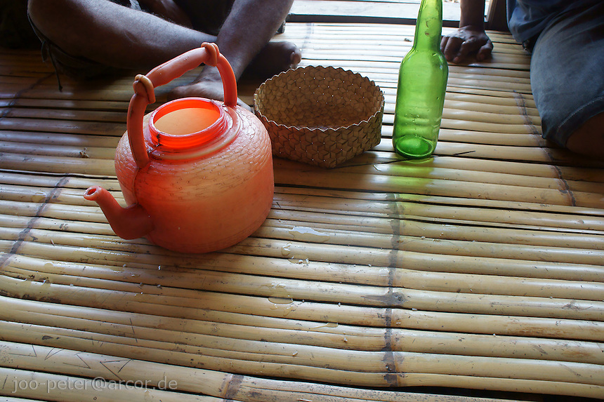food and drink is always shared and welcomes the guest - bamboo floor, wine bottle, water pot and food basket in village Bena, Ngada people, Flores, Indonesia