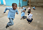 A refugee boy runs during physical education class in a school operated by St. Andrew's Refugee Services in Cairo, Egypt. Located at St. Andrews United Church of Cairo, the program is supported by Church World Service.