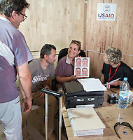 Andrea Antonelli, RN, A&E, Elvis Mehic, Operations and Logistics Liaison Officer, Joy Hardt, Chief Nursing Officer. Tour and set up printer and camera at a large ETU in Tubmanburg, Bomi County, Liberia on Wednesday, March 11, 2015.<br /> Occidental College professor Mary Beth Heffernan's PPE Portrait Project involves creating wearable portraits of the health care workers who must wear PPE (personal protective equipment) when working with patients.<br /> (Photo by Marc Campos, Occidental College Photographer) Mary Beth Heffernan, professor of art and art history at Occidental College, works in Monrovia the capital of Liberia, Africa in 2015. Professor Heffernan was there to work on her PPE (personal protective equipment) Portrait Project, which helps health care workers and patients fighting the Ebola virus disease in West Africa.<br />