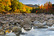 Autumn foliage along the East Branch of the Pemigewasset River in Lincoln, New Hampshire on a autumn morning. This location is just above the site of the old 1900s Gravity Dam that was linked to the Lincoln Mill era.