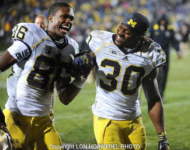 November 16, 2013: Michigan safety Thomas Gordon, right, celebrates the Wolverine's 27-19 triple-overtime victory over Northwestern with teammate Jehu Chesson, left, as they walk off the field, Saturday at Northwestern's Ryan Field in Evanston, IL.