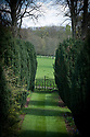 View down avenue of yew trees to ornamental iron gates, Hinton Ampner, Hampshire, late April.