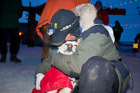 Rookie musher Chris Adkins  hugs his lead dog Vidalia  at the finish line in Nome after finishing in 50th place during the 2010 Iditarod