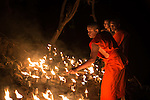 19 October 2013, Pakse, Laos:  Buddhist monks light candles on the riverbank of the Sedon River at Pakse following the Lao Airlines plane that crashed killing all on board. The aircraft crashed into the Mekong River tributary on approach to Pakse airport from Vientiane in severe weather killing all 44 passengers and 5 crew including six Australians. Rescue workers are still dragging the fast flowing river for further remains and the main body of the plane.  Picture by Graham Crouch