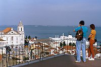 Portugal, Lisbon. Tourists takeing in view from Largo das Portas do Sol overlooking the Alfama district. Docked cruise ship of the Princess line in river Tejo. Lisbon, Portugal.