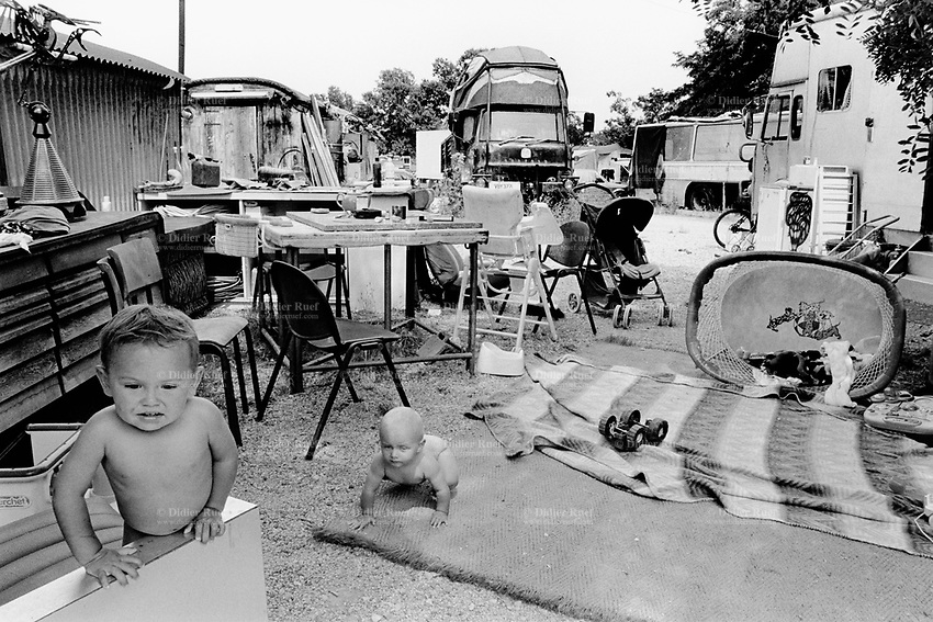 Italy. Province of Emiglia Romagna. Santarcangelo di Romagna. Mutoid Waste Company. Children play on the ground near the trucks which are their homes and houses. Using all types of industrial scrap for their raw materials the Mutoid Waste Company are a mobile and adaptable group of performance artists. Having the necessary equipment to allow them complete freedom, they have created an entirely new form of scultural-musical performance crossing the boundaries of circus, theatre and art.© 1999 Didier Ruef
