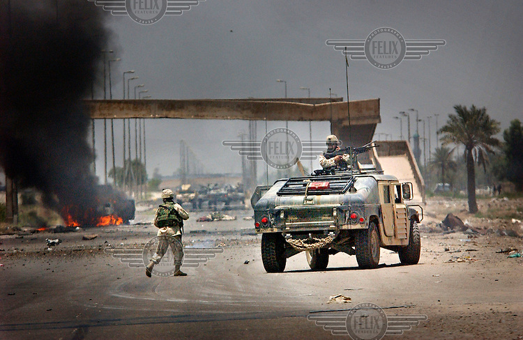 An attack on US forces in the Sadr City suburb. Shia fighters from the Mehdi army, the militia of radical cleric Moqtada al-Sadr, attacked a convoy of US soldiers from the 1st Cavalry. An RPG hit a Humvee which burst into flames, and then a secondary bomb was detonated at the roadside. Dead US soldiers have been retrieved and lie on the road a few metres to the right of the burning vehicle. This was one of the worst single attacks on US forces in Baghdad, with five soldiers being killed.