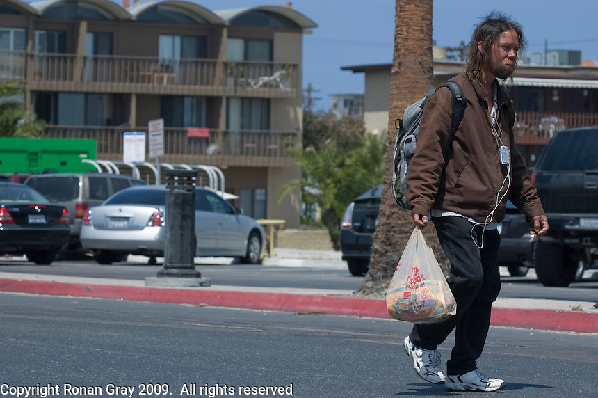 Tuesday, May 12, 2009.  Mission Beach, San Diego, CA, USA.  Mike Howell, a homeless man who collects recyclables in Mission Beach, walks along Santa Clara Avenue.  District 2 councilmember Kevin Faulconer announced today that he plans to use $80K of discretionary funds to continue a long-standing program of supplemental trash pick-ups from residents in Mission Beach during the summer months.