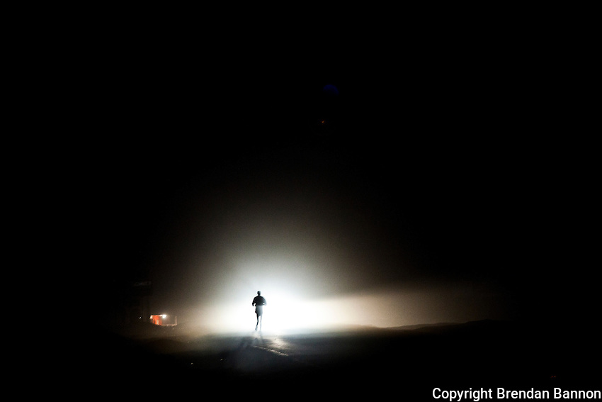 An athelete illuminated by headlights sets off  for a morning run in Iten, Kenya. The high altitude training town boasts some of the world's fastest runners at marathon,  half-marathon and 10,000 meters. Most runners begin the day before dawn with a training run of 15-18 km.