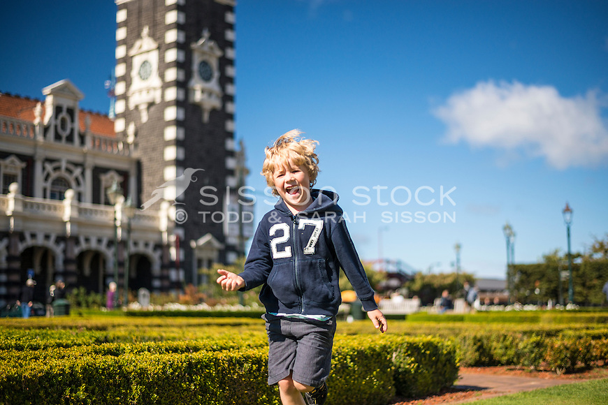 Young boy (6 years old) happy and leaping in the air outside the Dunedin Railway Station on a sunny blue sky day,  Otago, South Island, New Zealand - stock photo, canvas, fine art print
