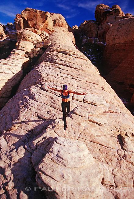 Woman runs along a rocky cliff. Calico hills area of Red Rock Canyon, Las Vegas Nevada
