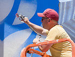 Bryce Chisholm paints during the Mural Marathon on Sunday July 1, 2018 in downtown Reno.