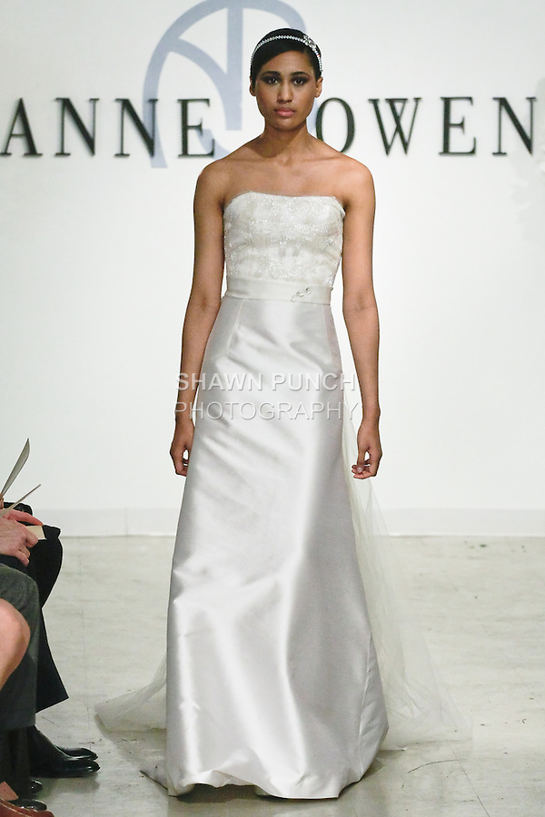 """Model walks runway in a Virtue Bridal dress - orchid white crystal beaded bodice, silk and wool strapless A-line gown with tulle train, and clear crstal belt, from the Anne Bowen Bridal Spring 2013 """"Coat of Arms"""" collection fashion show, during Bridal Fashion Week New York April 2012."""