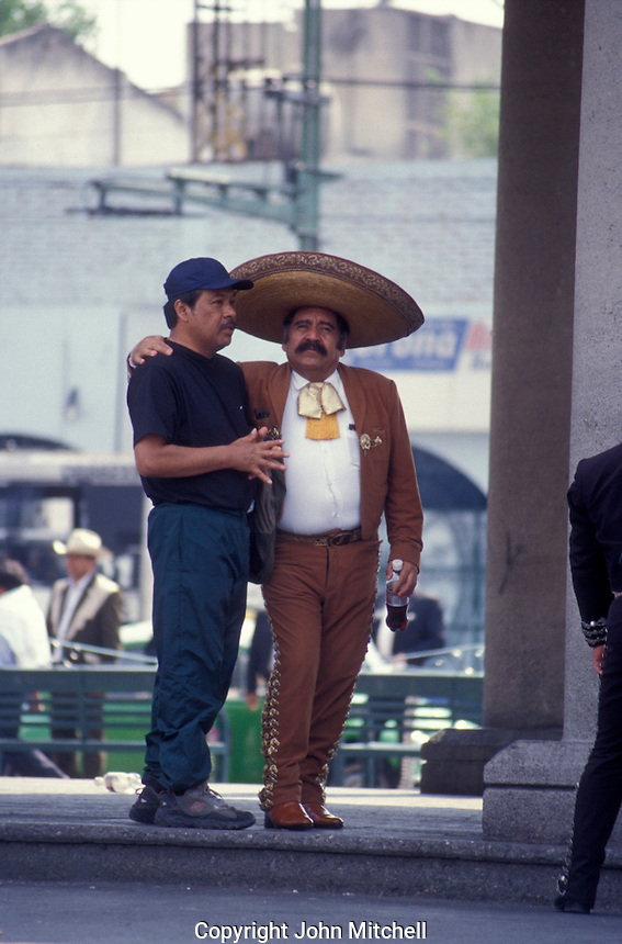 Mariachi player embracing a friend in Plaza Garibaldi, Mexico City, Mexico