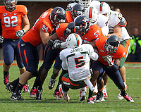 Oct 30, 2010; Charlottesville, VA, USA;   Miami Hurricanes running back Mike James (5) is stopped by several members of the Virginia Cavaliers defense during the game at Scott Stadium. Virginia won 24-19. Mandatory Credit: Andrew Shurtleff