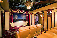 This home theater has a rich classic look and feel, ceiling lights, and comfortable theater chairs.