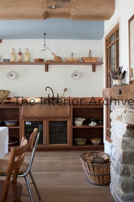 The copper sink unit and splashback which lines a wall of the kitchen was designed by Carina Cooper