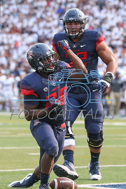 Arizona's Nick Wilson (28) celebrates with teammate Freddie Tagaloa (72) after scoring against Nevada during the first half of an NCAA college football game in Reno, Nev. on Saturday, Sept. 12, 2015. (AP Photo/Cathleen Allison)