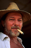 Amazon, Brazil. Old settler of European appearance wearing a straw hat and smoking a maize skin cigarette; Minas Gerais State.