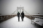 NEW YORK  - DECEMBER 19, 2008:  A couple walks across the Brooklyn Bridge during the first snow storm of the year on December 19, 2008 in New York City.    (Photo by Michael Nagle)