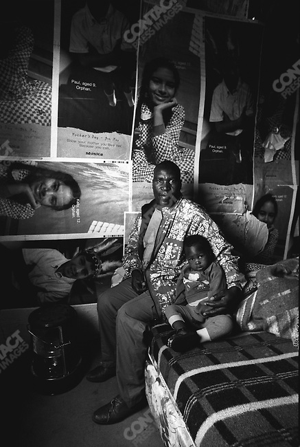 Ngadi Poposana, 39, with his son Awonke. Poposana's wife died of Aids; Khayelitsha township, Cape Town, South Africa, 2000.