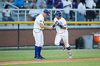 Gabriel Cancel (12) of the Burlington Royals shakes hands with third base coach Scott Thorman (16) after hitting a home run against the Princeton Rays at Burlington Athletic Stadium on August 12, 2016 in Burlington, North Carolina.  The Royals defeated the Rays 9-5.  (Brian Westerholt/Four Seam Images)