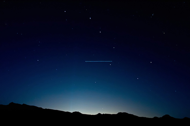 07 September 2009: NASA's STS-128 Space Shuttle Discovery (docked to the International Space Station) makes a visible pass through the Big Dipper with the lights of Las Vegas silhouetting the mountains as seen from Nelson, NV.