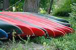 Canoes line up on land in preparation for use on a river trip.