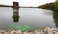 NWA Democrat-Gazette/DAVID GOTTSCHALK A fluorescein dye is visible Thursday, April 11, 2019, in Lake Fayetteville. Students from the University of Arkansas are studying Karst Hydrogeology and were conducting an experiment to trace leakage in the rocks on the dam. The environmentally friendly dye will color the lake water and dissipate within hours, flushing through the flow overnight.